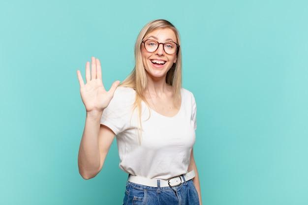 Jeune jolie femme blonde souriante joyeusement et joyeusement, agitant la main, vous accueillant et vous saluant, ou vous disant au revoir