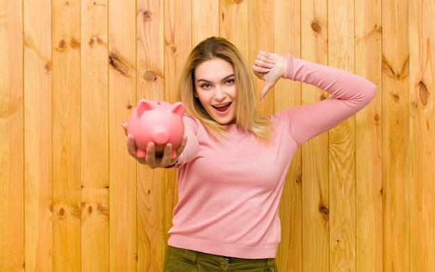 Jeune jolie femme blonde avec une tirelire contre le mur en bois