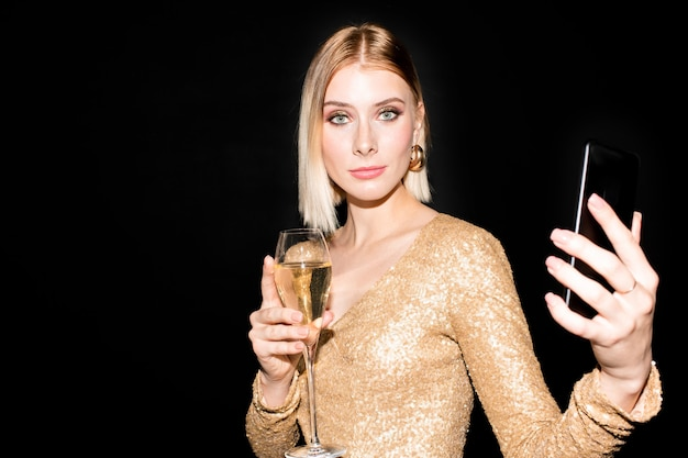 Jeune jolie femme blonde vous regarde tout en tenant le smartphone et la flûte de champagne et et profitant d'une fête d'anniversaire ou du nouvel an