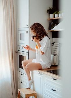 Jeune jolie femme boit du café assis dans sa cuisine à la maison et à l'aide de smartphone bénéficie de matin