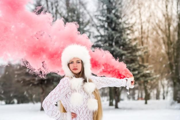 Jeune et jolie femme avec une bombe fumigène rouge dans le parc