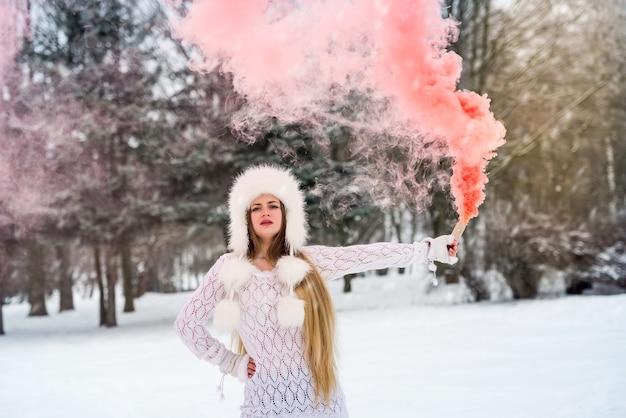 Jeune et jolie femme avec une bombe fumigène rouge