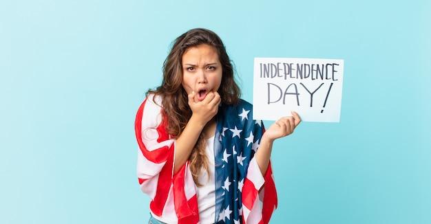 Jeune jolie femme avec la bouche et les yeux grands ouverts et la main sur le concept de la fête de l'indépendance du menton