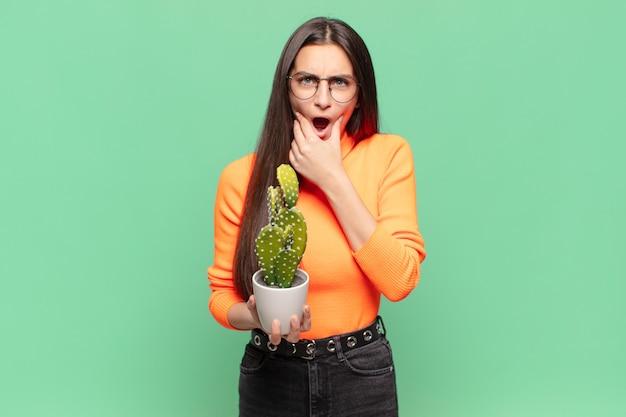 Jeune jolie femme avec la bouche et les yeux grands ouverts et la main sur le menton, se sentant désagréablement choquée, disant quoi ou wow. concept de cactus