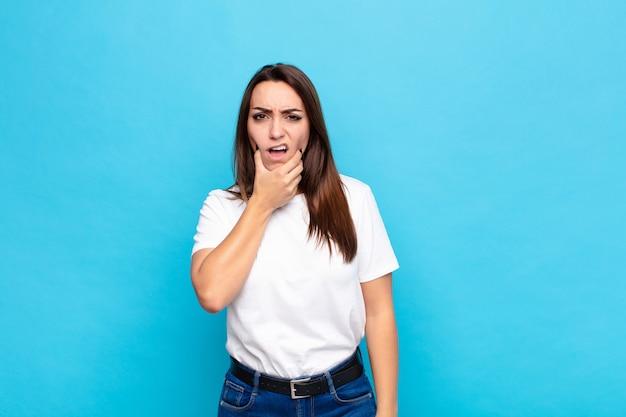 Jeune jolie femme avec la bouche et les yeux grands ouverts et la main sur le menton, se sentant désagréablement choquée, disant quoi ou wow contre le mur bleu