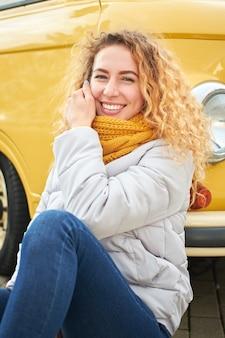 Jeune jolie femme bouclée rousse élégante implantation devant la voiture jaune et souriant