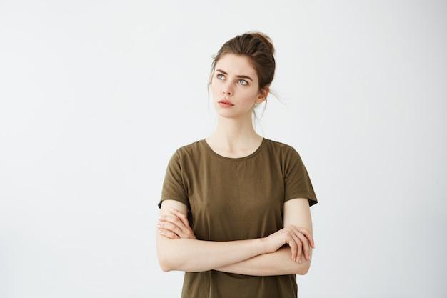 Jeune jolie femme avec les bras croisés pensant à la distance.