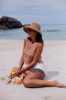 Jeune jolie femme bronzée caucasienne en vêtements tricotés et chapeau sur la plage