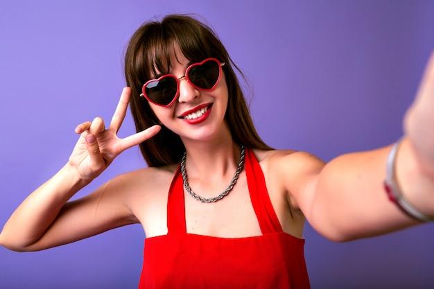 Jeune jolie femme brune aux cheveux longs et sourire étonnant faisant selfie sur fond violet, couleurs toniques vintage, tenue élégante rétro et lunettes de soleil coeur.