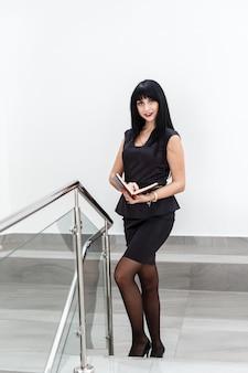 Jeune jolie femme brune heureuse vêtue d'un costume noir travaillant avec un cahier, debout dans un bureau, souriant.