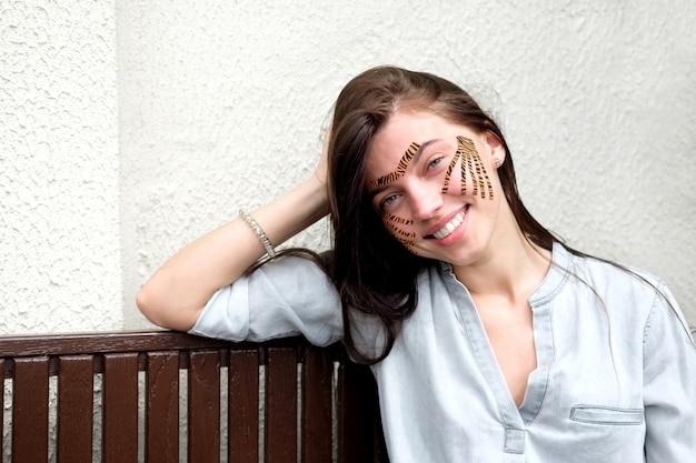 Jeune jolie femme brune souriante avec des bandes de couleur tigre après l'enregistrement du visage procédure dans un salon de beauté assis dans la rue