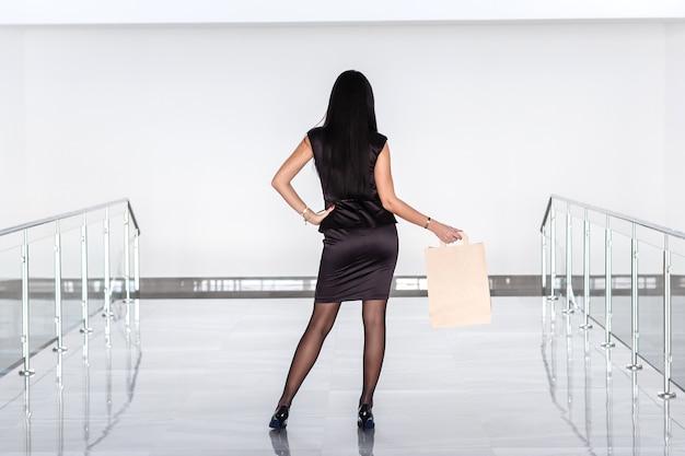 Jeune jolie femme brune vêtue d'un costume noir tenant un sac en papier, marchant sur le centre commercial. retour à la caméra.