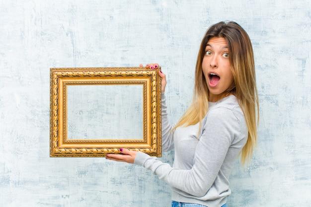 Jeune jolie femme avec un cadre baroque contre le mur de grunge