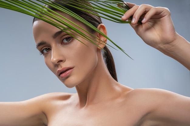 Jeune jolie femme calme derrière une plante exotique verte