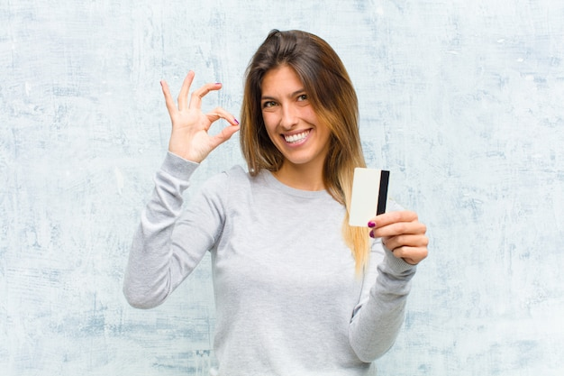 Jeune jolie femme avec une carte de crédit contre le mur de grunge