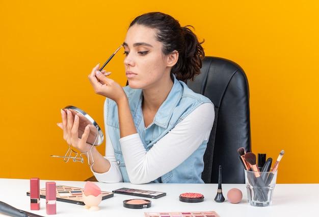Jeune jolie femme caucasienne assise à table avec des outils de maquillage appliquant un fard à paupières avec un pinceau de maquillage regardant un miroir