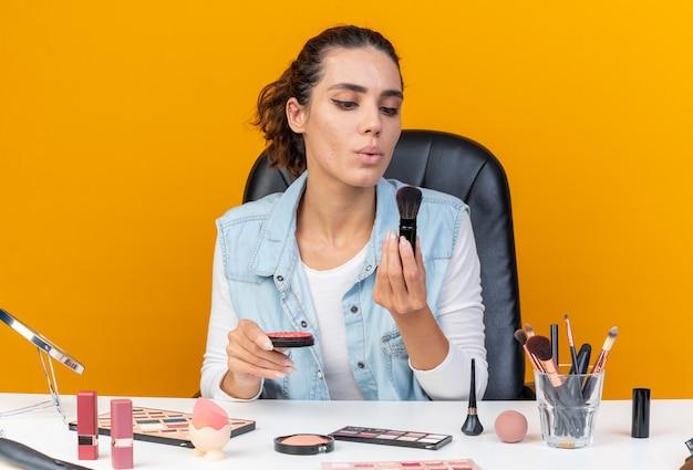 Jeune jolie femme caucasienne assise à table avec des outils de maquillage tenant du blush et soufflant sur un pinceau de maquillage