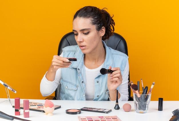 Jeune jolie femme caucasienne assise à table avec des outils de maquillage tenant un pinceau de maquillage et regardant le fard à joues