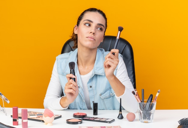 Jeune jolie femme caucasienne assise à table avec des outils de maquillage tenant et regardant des pinceaux de maquillage