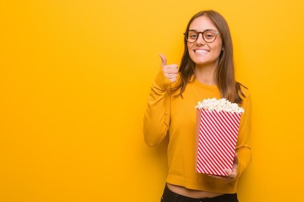 Jeune jolie femme caucasienne souriante et levant le pouce. elle mange des popcorns.