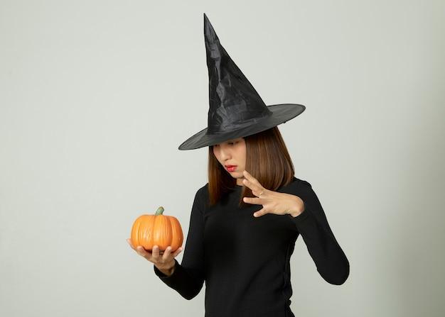 Jeune jolie femme avec chapeau de sorcière tenant halloween citrouille jack o lantern décor