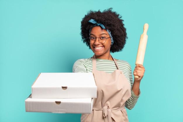Jeune jolie femme chef afro avec un rouleau à pâtisserie et des pizzas