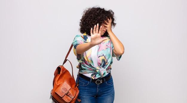 Jeune jolie femme avec une chemise colorée et un sac à dos