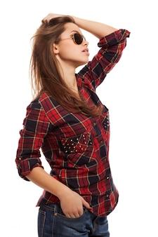 Jeune jolie femme en chemise et lunettes de soleil
