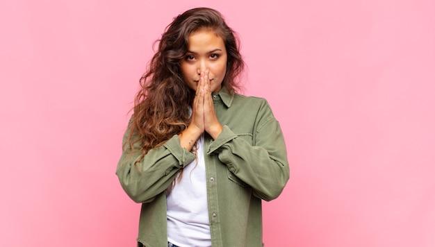 Jeune jolie femme avec une chemise ouverte en jean vert posant sur un mur rose