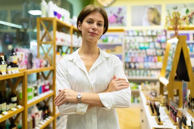 Jeune jolie femme en chemisier blanc est debout dans un magasin de cosmétiques près des étagères avec des produits