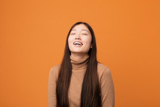 Jeune jolie femme chinoise détendue et heureuse en riant, cou tendu montrant les dents.
