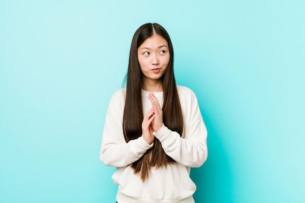 Jeune jolie femme chinoise faisant un plan à l'esprit, mettre en place une idée.