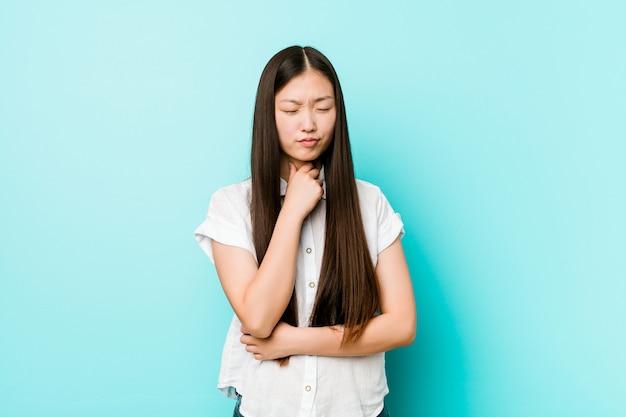 Jeune et jolie femme chinoise souffre de douleurs à la gorge causées par un virus ou une infection.