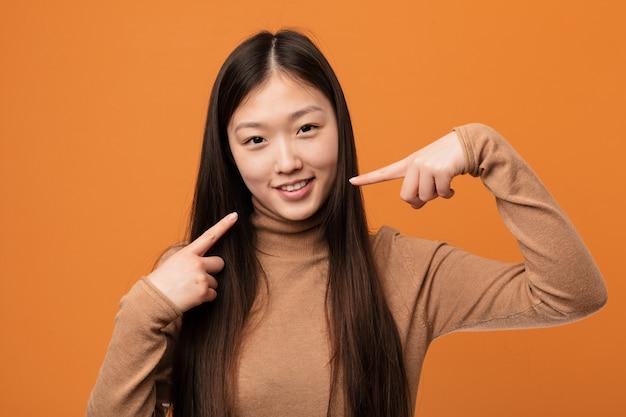 Jeune jolie femme chinoise sourit, pointant ses doigts vers la bouche.