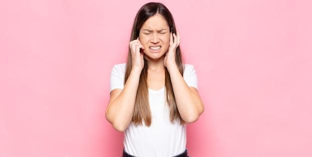 Jeune jolie femme à la colère, stressée et agacée, couvrant les deux oreilles à un bruit assourdissant, un son ou une musique forte