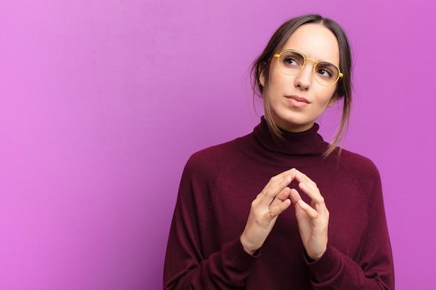 Jeune jolie femme complotant et complotant, pensant des astuces et des tricheurs sournois, rusé et trahissant sur le mur violet