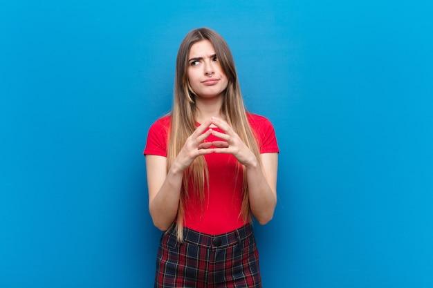 Jeune jolie femme complotant et complotant, pensant des trucs et astuces sournois, rusé et trahissant contre le mur bleu