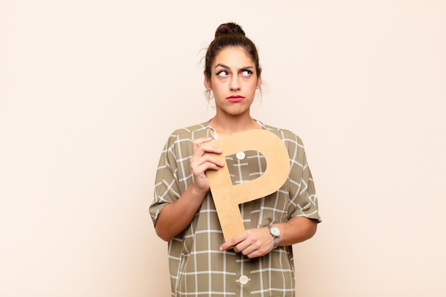 Jeune jolie femme confuse, douteuse, pensant, tenant la lettre p de l'alphabet pour former un mot ou une phrase.