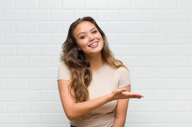 Jeune jolie femme contre le mur blanc