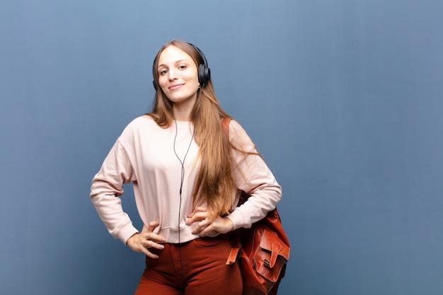 Jeune jolie femme contre un mur bleu avec un espace de copie
