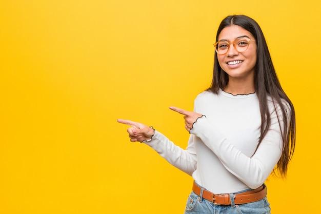 Jeune jolie femme contre un mur jaune excité pointant avec les index loin