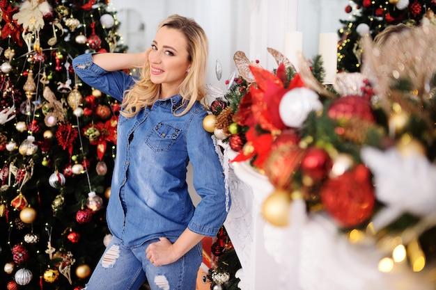 Jeune jolie femme en costume en jean avec des cheveux blonds sourit dans le contexte d'un sapin de noël