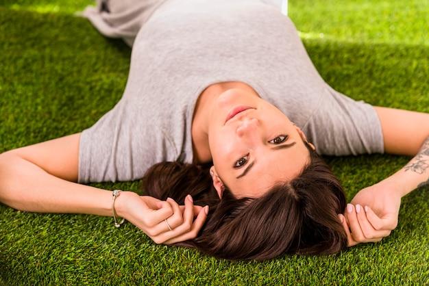 Jeune jolie femme couchée sur la pelouse