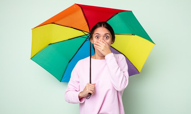 Jeune jolie femme couvrant la bouche avec les mains avec un choc. concept de parapluie