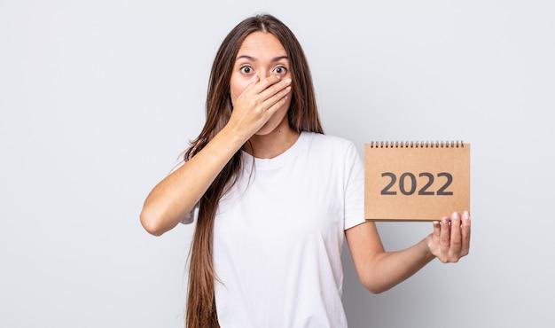 Jeune jolie femme couvrant la bouche avec les mains avec un choc. concept de planificateur 2022