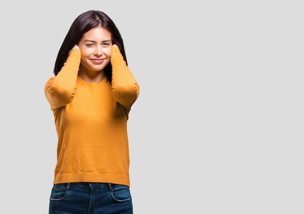 Jeune jolie femme couvrant les oreilles avec les mains, en colère et fatiguée d'entendre du son