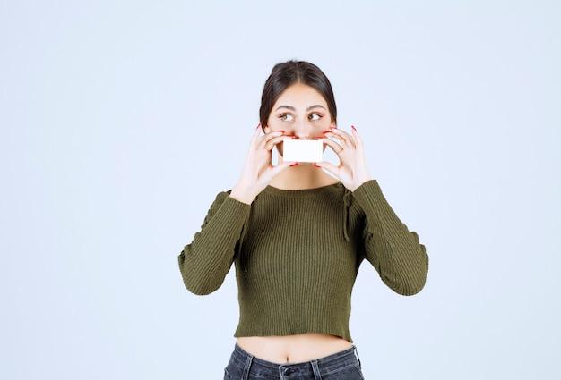 Jeune jolie femme couvrant sa bouche avec une carte de visite vierge.
