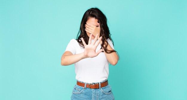 Jeune jolie femme couvrant le visage avec la main et mettant l'autre main devant pour arrêter l'appareil photo, refusant des photos ou des images