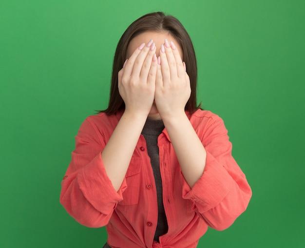 Jeune jolie femme couvrant le visage avec les mains isolées sur le mur vert