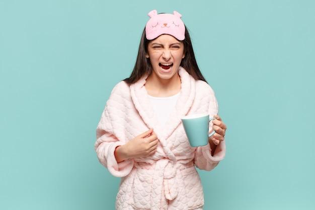 Jeune jolie femme criant agressivement, l'air très en colère, frustrée, indignée ou agacée, criant non. concept de réveil en pyjama